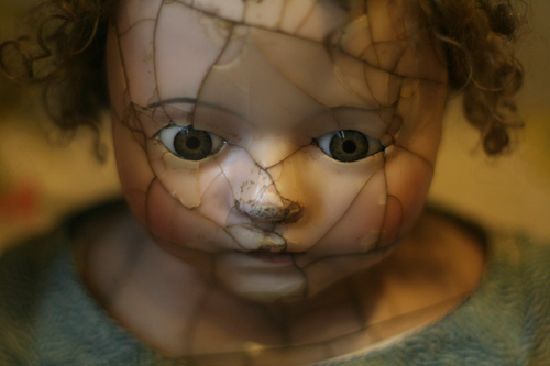 Photo of antique procelain doll wil cracks on face