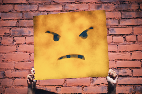 Hands holding an angry face sign