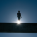 silhoutte of man on bridge with rising sun behind him