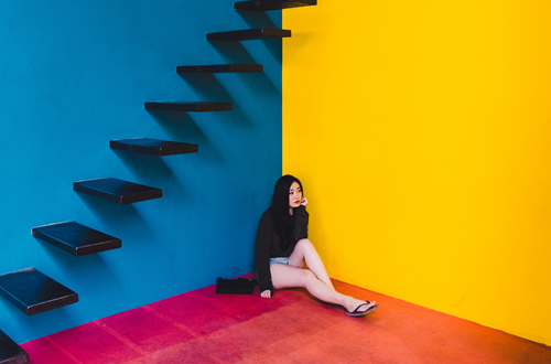 Sad woman sitting under stairs in colorful room