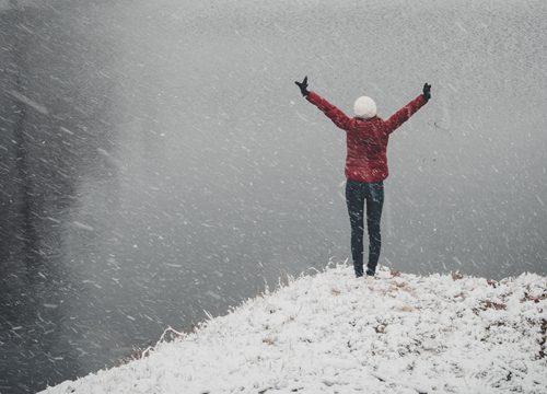 woman in victory pose at top of snowy hilltop